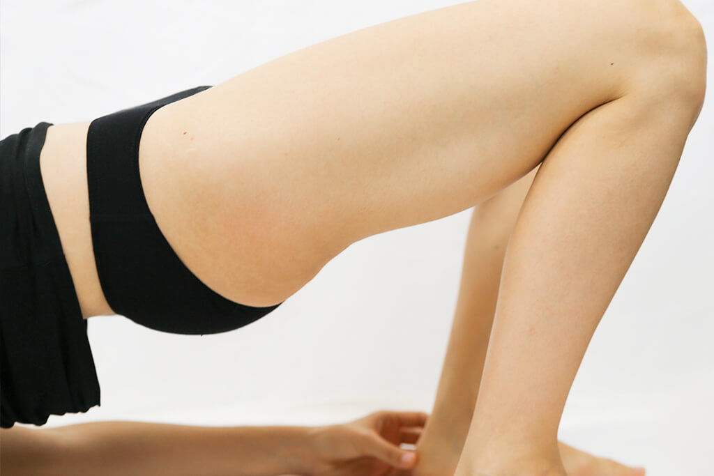 Frau in Yogapose gegen Inkontinenz