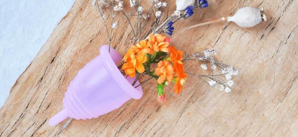 Menstruationstasse mit Blumen auf Holz