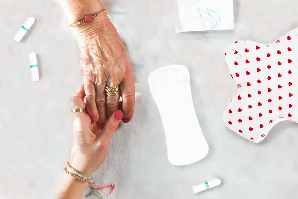 Mutter und Tocher halten Hände mit Menstruationsprodukte