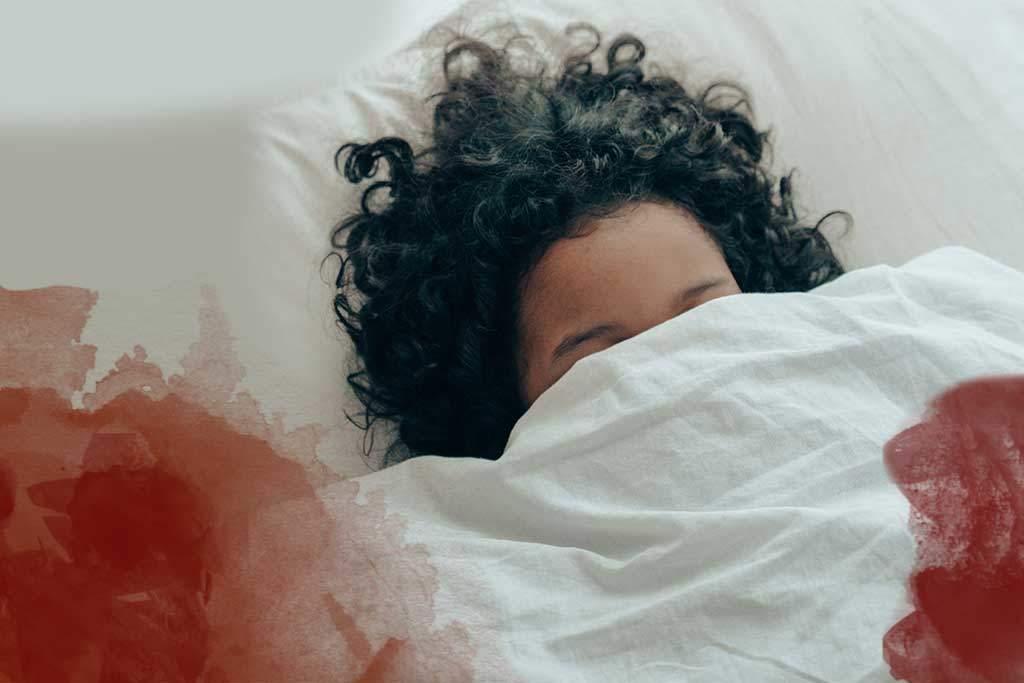 Frau im Bett mit Periodenblut